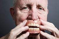 Senior holding false teeth in front of his mouth