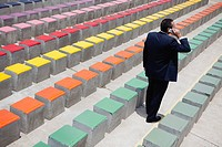Business executive using cell phone by rows of bleachers, rear view
