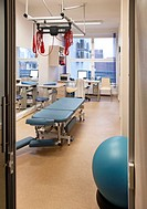 Rehabilitation Center facilities. A treatment room, with a long high narrow table, and overhead grid. A patient lift or mechanical hoist. Red harness....