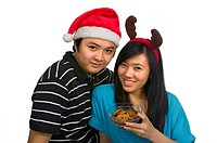 Chinese couple celebrating christmas by eating cookies isolated over white background