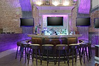 Round bar stand against three TV screens on brick wall