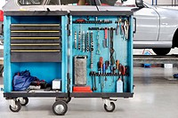 Tool cart with wrenches, screwdrivers, socket spanners, a can of lubricant and spare parts drawers. Organised storage for workshop equipment. A car on...