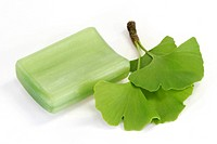 Close_up of ginkgo leaves and a piece of soap on white background