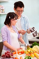 Asian couple looking at USG fetus picture in the kitchen