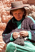South America, Argentina, Province Jujuy _ peasant woman, sewing on the street of a tiny and remote village, Susques, in the Puna.