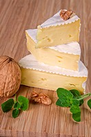 Cut camembert pieces arranged on wooden board.