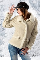 fashion studio pretty young woman with white fur jacket and a nice black cap