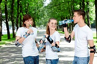 Young people in equipment in park drink water