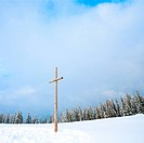 winter snowy fir trees on mountainside on overcast sky background and wooden cross in front Carpathians, Ukraine, photo in square proportions