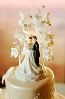 Bride and Groom cake toppers on a wedding cake with floral accents