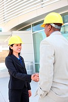 An attractive man and woman architect team on construction site handshake
