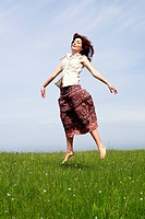 Young woman jumping on a beautiful green meadow