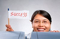 Happy woman holding success flag made of paper and pencil