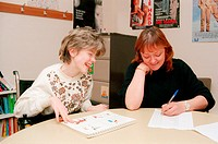 Teacher and girl with learning difficulties, who is wheelchair user, sitting at desk in classroom laughing,