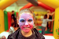 Teenage girl at youth club with face painted, children on bouncy castle in background