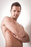 uomo a torso nudo con braccia conserte