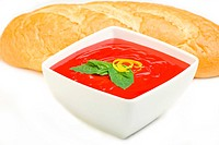 Tomato soup served with basil and bread