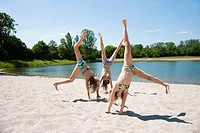 Girls doing gymnastics on the beach of a lake