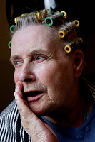 Elderly woman in the hairdressers wearing curlers