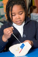 Primary school pupil learning to sew during a needlework lesson at school,