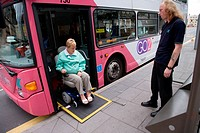 Bus driver ensuring woman wheelchair user descends ramp from the bus safely