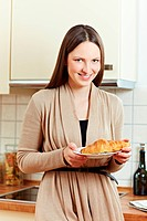 Happy woman eating a croissant in a kitchen