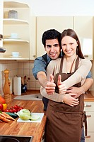 Smiling young couple holding their thumbs up in a kitchen