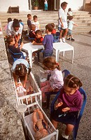 Nursery school children playing with dolls in playground,