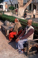 Men with learning disabilities sitting on bench in the grounds of the Apahaj Ashram, Patiala, Punjab, India,
