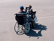 Wheelchair user towing another wheelchair user