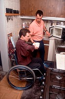 Man with disability, who is wheelchair user, preparing meal in kitchen with carer,