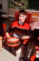 Young boy with disability, who is wheelchair user, playing drum in school music lesson,