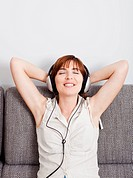 Beautiful young woman at home listening music with headphones