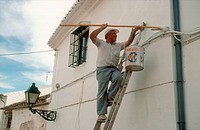 Man painting the outside of a house in Antequera, Andalucia,