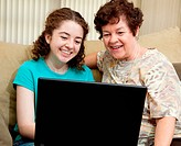 Teen girl and her mother enjoy using a laptop computer.