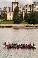 children paddle two large canoes toward False Creek, Vancouver, BC, Canada