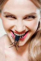 Young woman biting plastic beetle