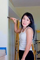 Asian woman contractor painting a wall