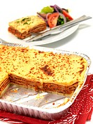 A tray of lasagne isolated against a white background