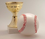 Little golden trophy near a baseball
