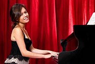 Beatiful young woman playing piano, looking into the camera, with a warm and disarming smile