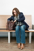 Young woman looking for something in her purse, sitting on a wooden bench in the waiting room of a medical clinic