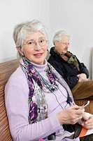 elderly woman with a portable mp3 player sitting on a bench in a hospital's waiting room
