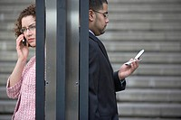 Businessman and Woman Using Cell Phone