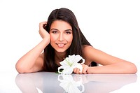a portrait of a young woman, posing on a white background. she has her arms on a white table and resting her head on one of her hands. she is smiling ...