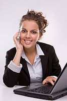 smiling business girl using a laptop computer and talking on the phone