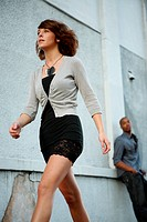 A young woman walking in the city while a man in the background checks her out.