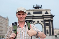 Tourist with backpack against Triumphal arch in Moscow