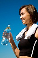 A beautiful sporty caucasian girl carrying a water bottle after exercise on the beach