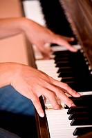 A shot of a man practicing playing piano
